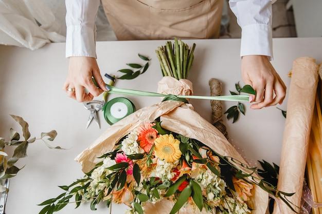 Флористка завязывает ленточный бант на букет цветов, завернутый в крафт-бумагу на рабочем столе