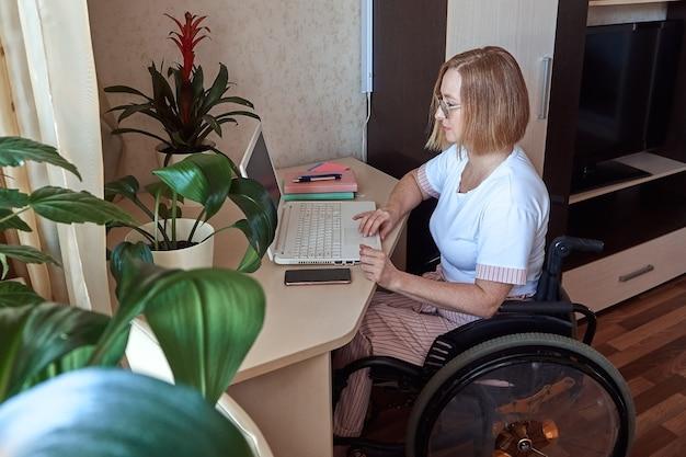 車椅子で身体障害者の女性フリーランサーが自宅からリモートで働く