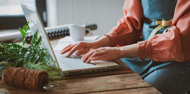 안경과 앞치마를 입은 여성 정원사, 콘크리트 슬래브에 나무 테이블에 앉아 노트북을 사용하여 작업