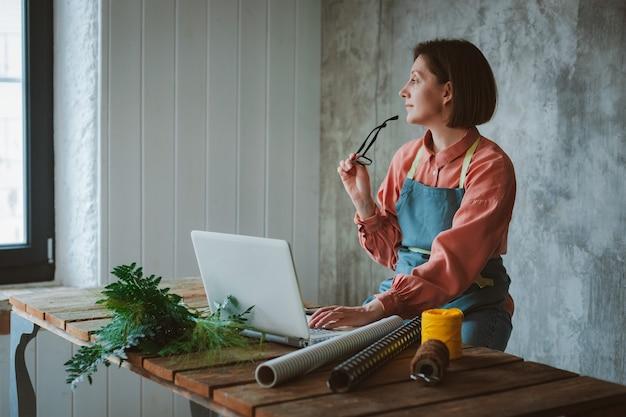 眼鏡とエプロンを身に着け、コンクリートスラブに対して木製のテーブルに座って、ラップトップを使用して仕事をしている女性の庭師