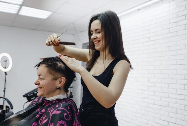 女性美容師が美容院で女性の髪の毛の端を丁寧にカット、クローズアップ