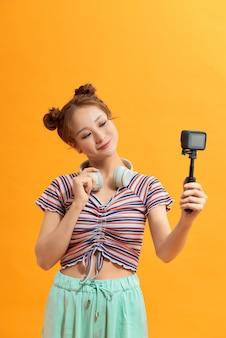 여성의 손에는 익스트림 액션 비디오 사진에 자주 사용되는 작은 액션 카메라가 있습니다.