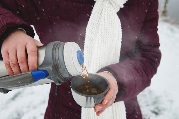 魔法瓶を持って温かい飲み物を持ち、熱いお茶を金属製のマグカップに注ぐ女性の手。雪の降る冬の日