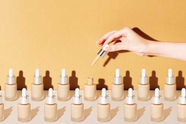 여성 손은 bb 파운데이션 크림을 바르기 위한 스포이드를 들고 있습니다. 베이지색 배경에 화장품 메이크업 제품의 열리고 닫힌 항아리. 미용 제품 포장의 패턴입니다.