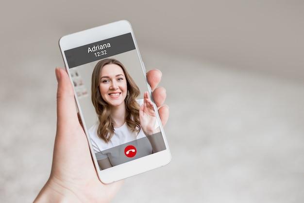Женская рука держит мобильный телефон с девушкой на экране, видеочат. женщина делает видеозвонок своему другу. счастливая молодая девушка улыбается на экране телефона, интерфейс, кнопки вызова