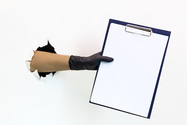 Женская рука в черной латексной перчатке сквозь рваную бумагу на белом фоне держит планшет для бумаги формата а4. карантинные меры по предотвращению распространения covid 19. рука в перчатке сквозь рваную бумагу.