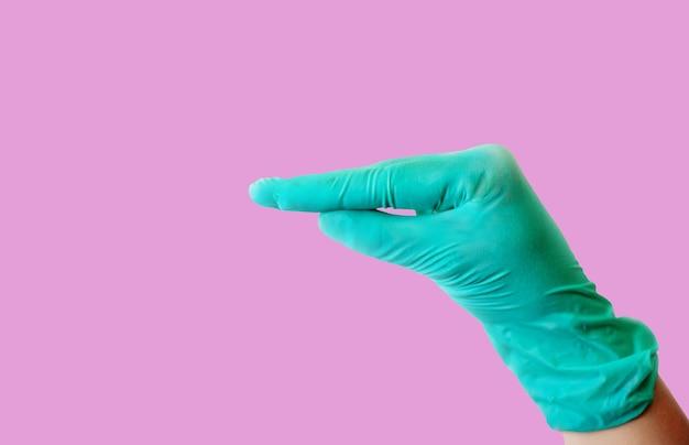 青いラテックス手袋をはめた女性の手は、アヒルのくちばしに似たジェスチャーをします