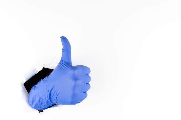 Женская рука в синей резиновой перчатке показывает классу сквозь рваную дырку в белой бумаге. пальцы вверх - все будет хорошо. копировать пространство