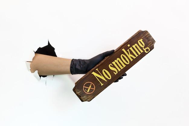 Женская рука в латексной черной перчатке в разорванном отверстии на белом фоне держит деревянный знак для некурящих. карантинные меры по предотвращению распространения covid 19. рука в перчатке через разорванную бумагу