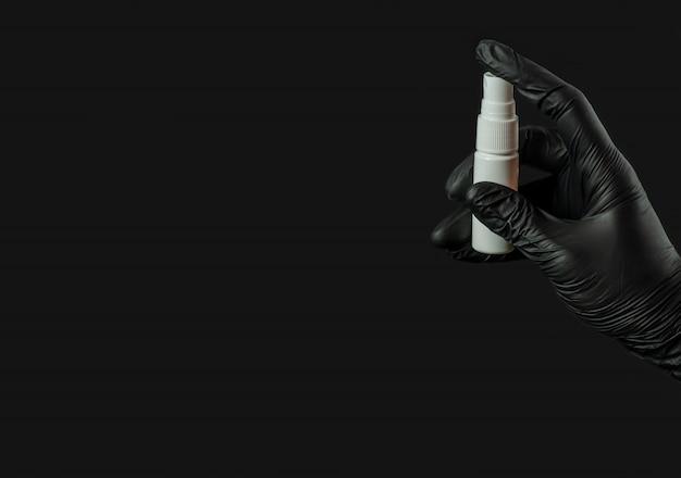 Женская рука в резиновой черной перчатке держит флакон с антисептиком для рук на черной поверхности