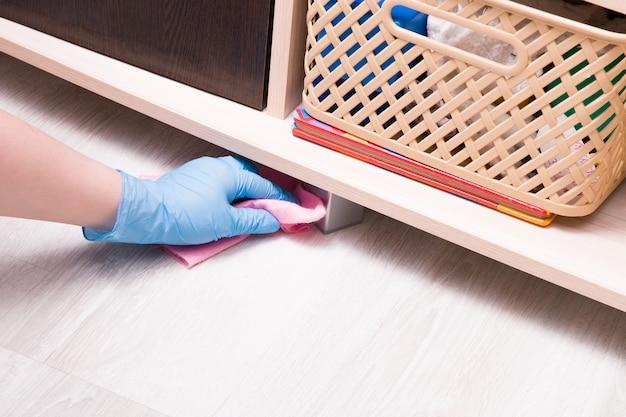 ピンクのぼろきれが付いているゴム製の使い捨て手袋の女性の手は、食器棚の下のほこりを拭きます