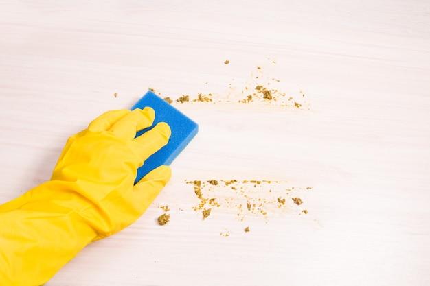 노란색 고무 장갑의 여성 손은 나무 테이블에 남은 음식을 설거지하기 위해 파란색 스폰지로 닦습니다.