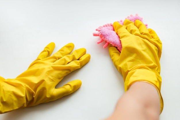 분홍색 극세사 걸레가 달린 노란색 고무 장갑을 낀 여성 손이 흰색 표면을 씻고 닦습니다. 봄, 정기 일반 청소. 욕실 청소 개념입니다. 고품질 사진