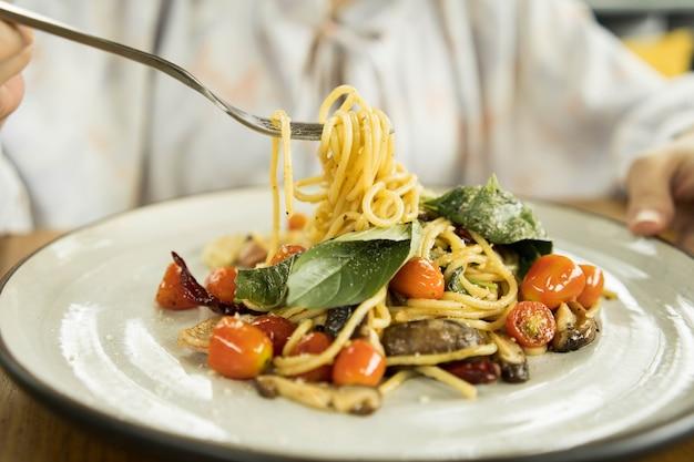 Женская рука пытается использовать вилку, чтобы съесть острые спагетти с беконом и базиликом, посыпанные тертым сыром в белом блюде.