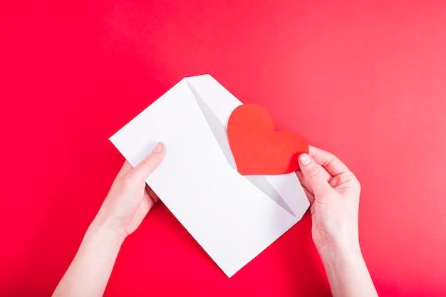 Женская рука открывает конверт с красным сердцем на красном столе. любовное письмо любимой. признание в любви. валентина приглашение. вид сверху. плоская планировка.