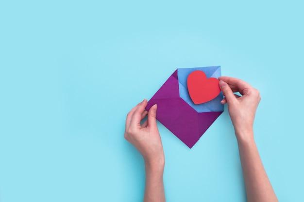 여성 손 분홍색 배경에 붉은 마음으로 봉투를 엽니 다. 사랑하는 사람에게 보내는 연애 편지.