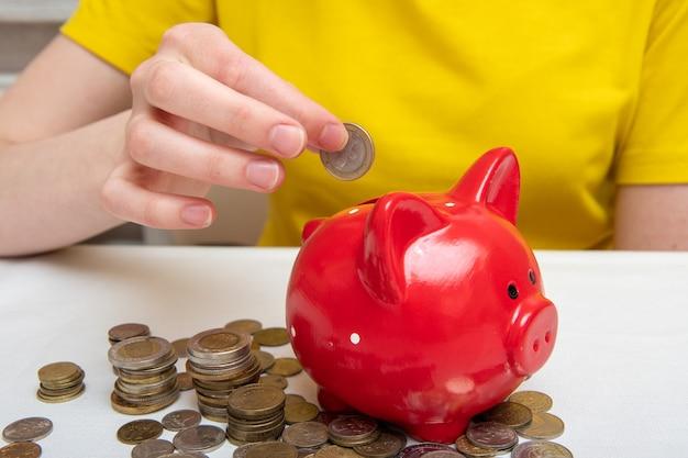 Женская рука кладет деньги в щель красной копилки, на столе много монет разных стран. концепция экономии.