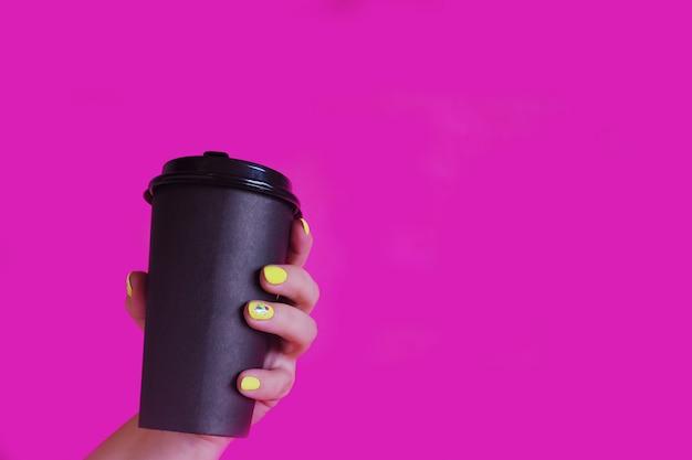 明るい黄色のマニキュアを持つ女性の手は、明るいピンクの背景にコーヒーと黒いカップを保持しています。コピースペース。
