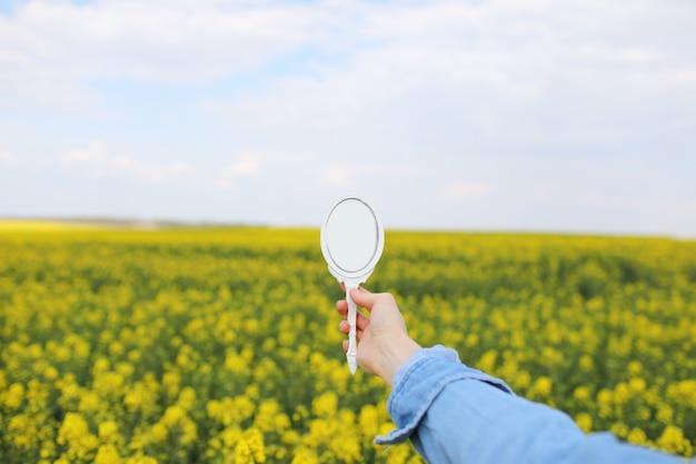 Отражается женская рука с миниатюрным ретро-зеркалом в поле желтых полевых цветов.
