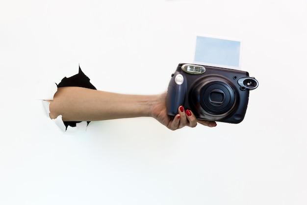 白い背景の破れた穴に赤いマニキュアを持つ女性の手がカメラを保持します。