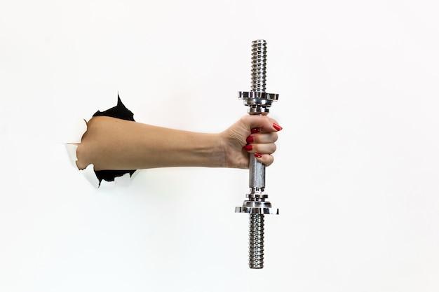 白い背景の破れた穴に赤いマニキュアを持つ女性の手はダンベルを保持します