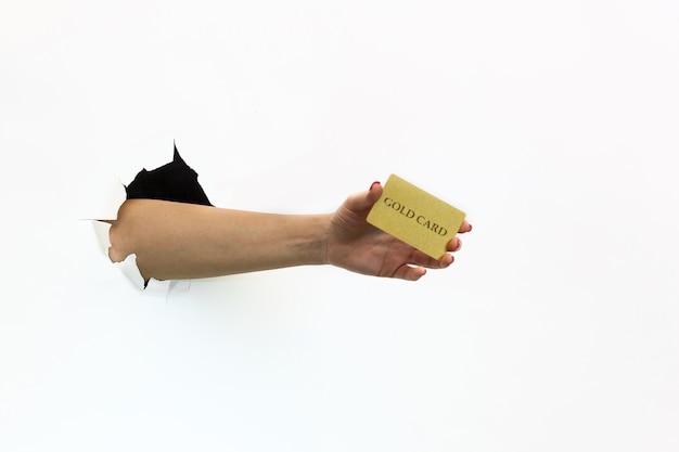 白い背景の破れた穴に赤いマニキュアを持つ女性の手は、金の銀行カードを保持しています。破れた白い紙を手渡します