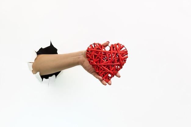 引き裂かれた白い紙を通して赤いマニキュアを持つ女性の手は赤い心を持っています