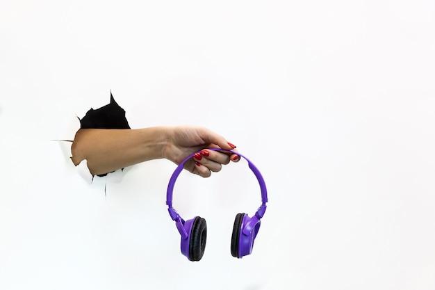 찢어진 흰 종이에 빨간 매니큐어를 바른 여성의 손에는 무선 보라색 헤드폰이 있습니다. 찢어진 흰 종이를 통해 손