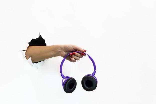 찢어진 흰 종이에 빨간 매니큐어를 바른 여성 손이 무선 보라색 헤드폰을 들고 있다