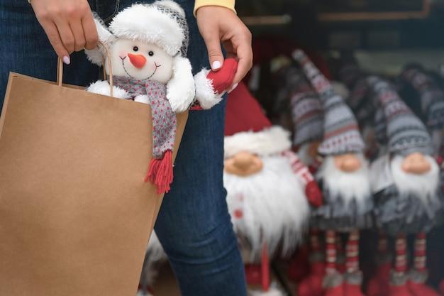 Женская рука несет в магазине бумажный пакет с елочной игрушкой-снеговиком. концепция нового года