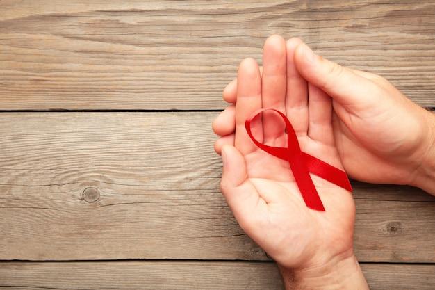 エイズの赤いリボンを保持している女性の手