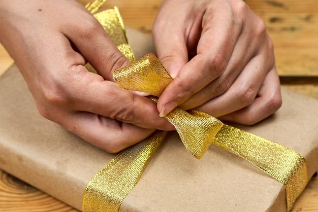 Женские руки упаковывают рождественский подарок. делайте рождественские подарки. рождественские подарки своими руками друзьям и родным