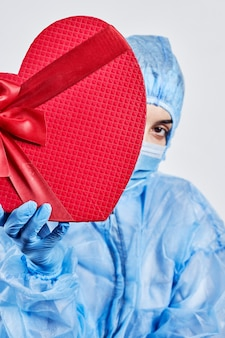 Медицинский работник-женщина получает подарок на день святого валентина на работе
