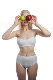 白い壁に隔離された異なる腕に赤と緑のリンゴを保持している女性。デンタルケアのコンセプト