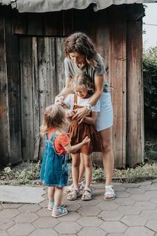 女性のホステスが庭で娘と一緒に新しく生まれた黄色の鶏の世話をします。家庭農業
