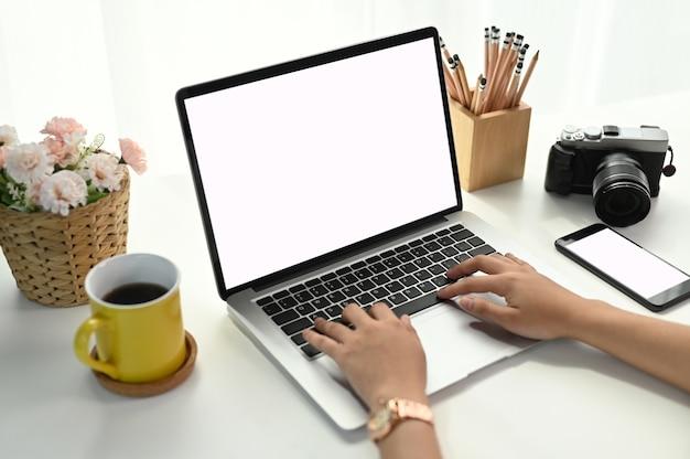 Женщина печатает на клавиатуре на белом столе в своем офисе