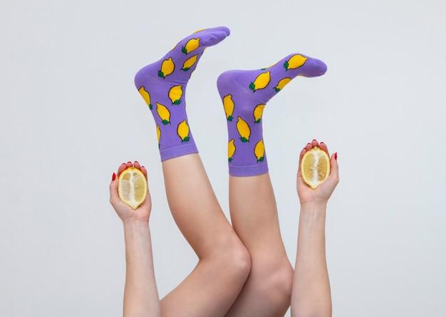 흰색 배경에 고립 된 레몬과 함께 다채로운 양말에 여성 다리