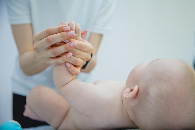 흰색 티셔츠를 입은 여성 안마사가 마사지 실에서 아기에게 손잡이 마사지를 제공합니다.