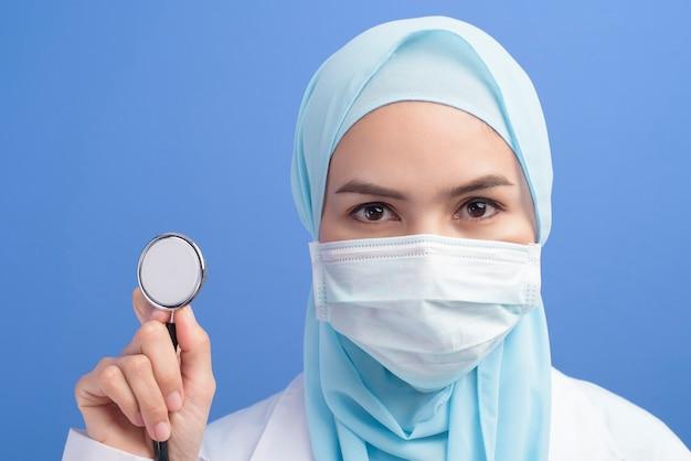 青い壁にサージカルマスクを着用したヒジャーブの女性イスラム教徒の医師