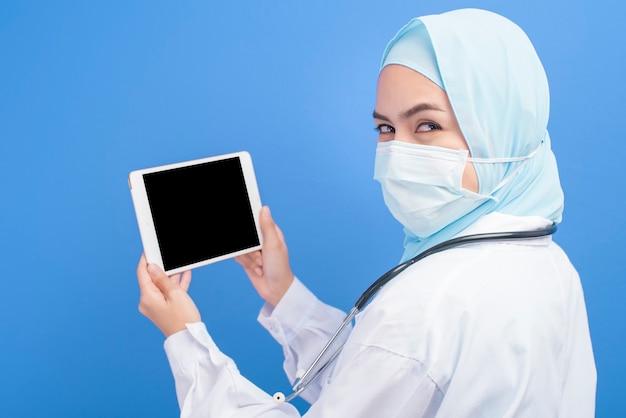 青の上にタブレットを使用してサージカルマスクを身に着けているヒジャーブを持つ女性のイスラム教徒の医師