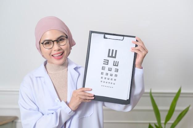 Женщина-офтальмолог-мусульманка держит тест на зрение для измерения остроты зрения