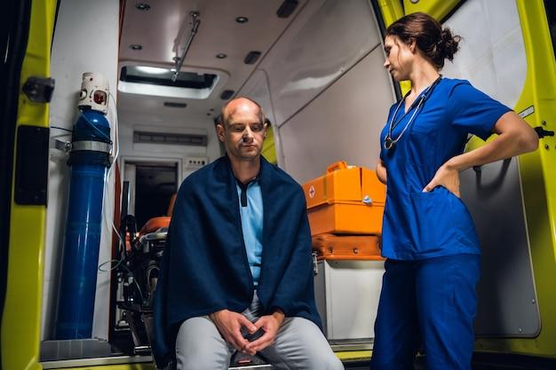 火事から救出された負傷した男性に応急処置を提供する女性の救急救命士。