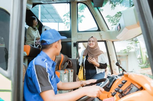 バスに乗っている運転手に見られたとき、ベールに乗った女性の乗客がバスに乗りました