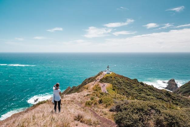 Женщина-фотограф делает снимок красивый пейзажный пейзаж с синим небом в горах и маяком, историческим зданием. мыс рейнга, северный остров, новая зеландия.