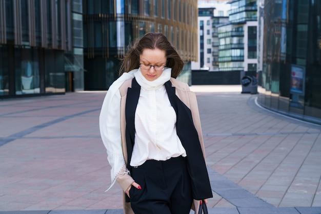 세련된 비즈니스 복장을 한 백인 비즈니스 여성의 여성 초상화가 근처 안경에 서 있다