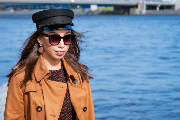 彼女の手に新聞とサングラスと茶色のジャケットと黒の帽子の美しいブルネットの女性と晴れた春の日の堤防にヨーロッパの外観の女性の肖像画