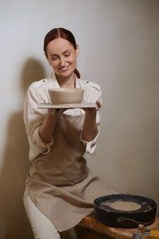 Женщина-гончар в своей мастерской участвует в гончарном процессе