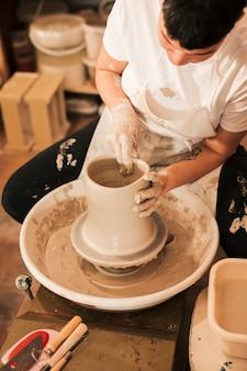 女性の陶工は、陶芸家の輪の上で粘土を扱う