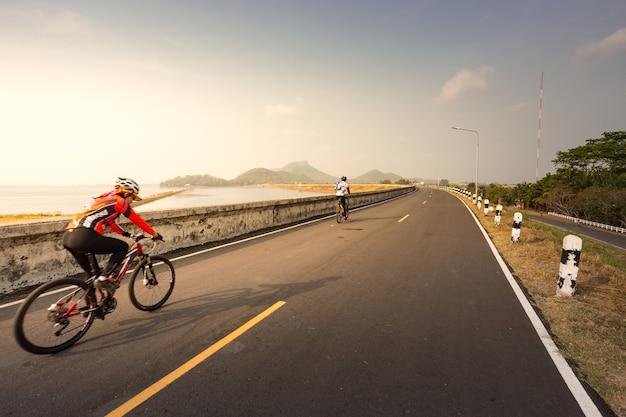 朝、女性がダム道路を自転車で走る