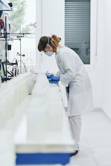 安全マスク、白いローブ、青いラボ用手袋を着用し、焦点の合っていないサンプルボトルの長い列の後ろにメモをとる女性科学者。浅い被写界深度